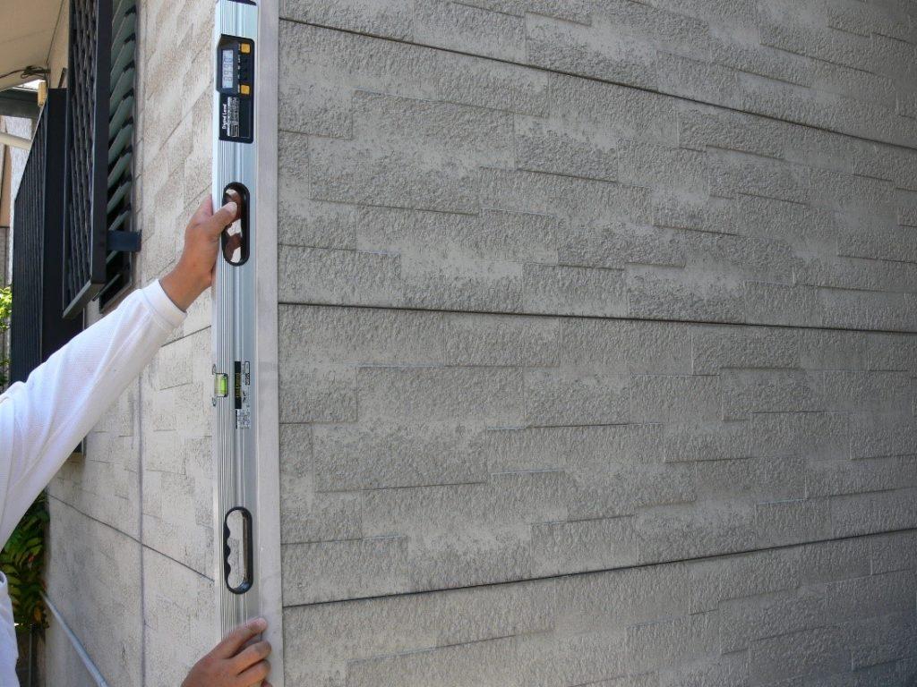 建物の傾斜度を測定している写真(塗装工房)